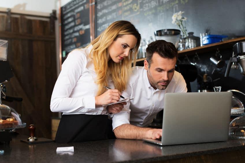 יועץ אסטרטגי עובד על לפטופ עם עובדת בבית קפה